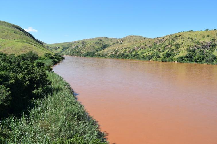 Der Tsiribihina hat sich durch die Sedimente rot gefärbt. Die Berge im Hintergrund sind alle kahl.